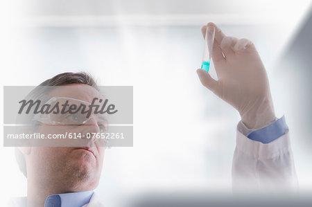Scientist looking at test tube