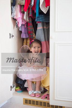 Girl in princess costume hiding in cupboard
