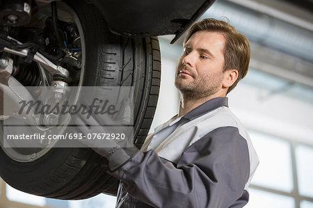 Mid adult technician adjusting car's tire in workshop
