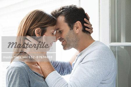 Couple cuddling by open window