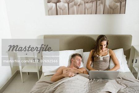 Woman using laptop in bed, man asleep
