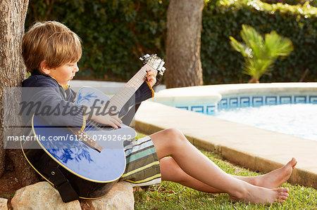 Boy playing guitar by pool