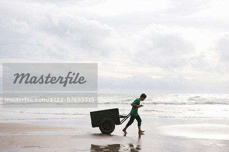 Man on Beach pulling Cart in sunset