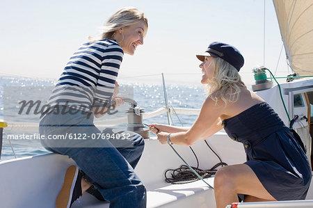 Smiling women sailing on boat