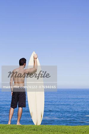 Man holding surfboard by ocean