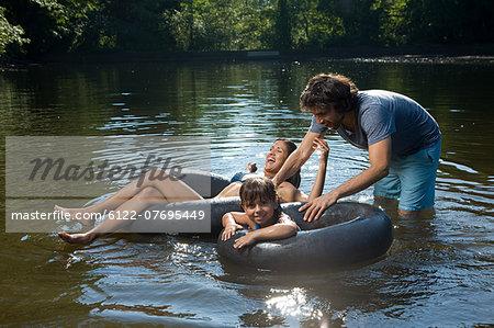 Couple and daughter having fun in lake