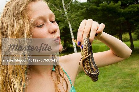 Teenage girl holding small snake