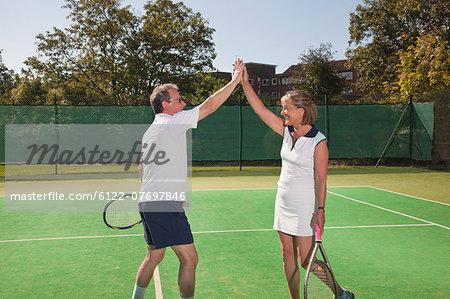 Senior couple hi-fiving on tennis court