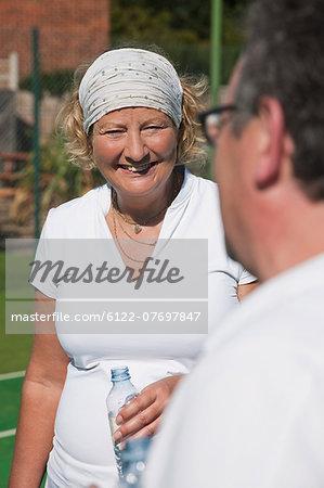 Senior and mature adults enjoying drink on tennis court