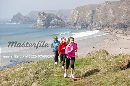 Family running on cliffs over beach