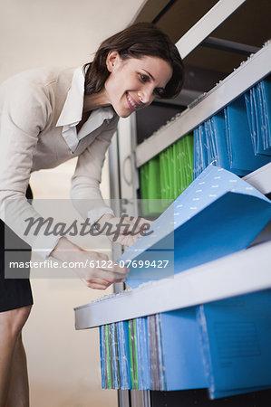 Businesswoman reading files in folders