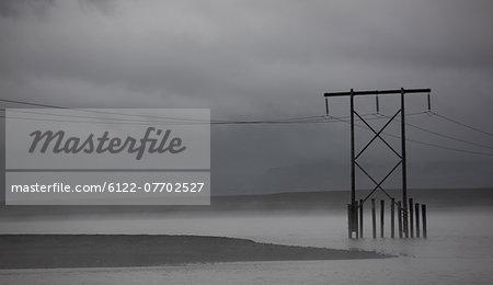 Powerlines in foggy rural landscape