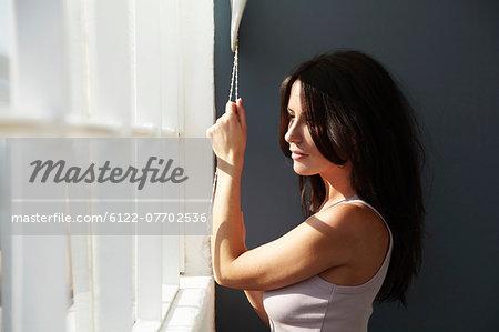 Smiling woman raising blinds