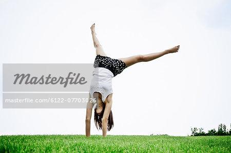 Woman doing cartwheel outdoors