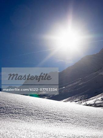 Sun shining over snowy landscape