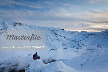 Hiker resting above glacial hot spring