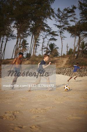 Boys playing soccer on sandy beach