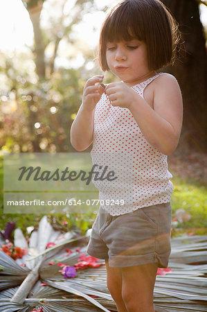 Girl holding green anole lizard in garden