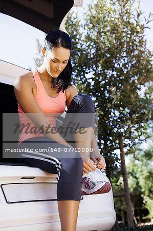Female jogger tying shoelace at back of car