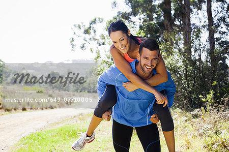 Female jogger riding piggyback on man