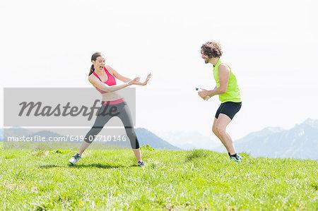 Male jogger squirting water at woman, Wallberg, Tegernsee, Bavaria, Germany