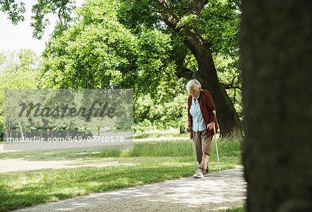 Senior woman walking through park, using walking stick