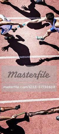 Relay runners handing off baton on track
