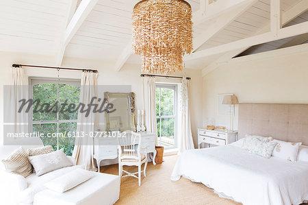 Chandelier and armchair in rustic bedroom