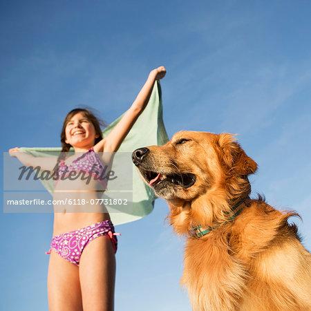 A girl in a beach towel with a golden retriever dog.