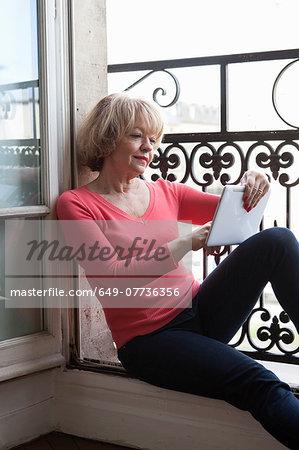 Woman using digital tablet at balcony