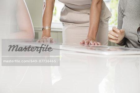 Cropped shot of three businesswomen and blueprint