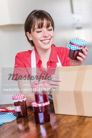 Woman packing homemade strawberry jam