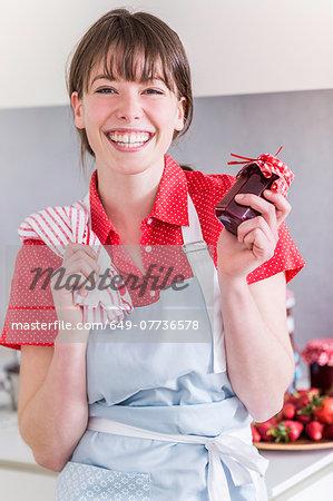 Woman holding up jar of homemade strawberry jam