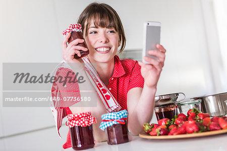 Woman taking selfie with strawberry jam jar