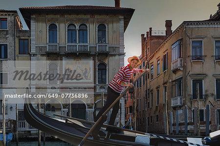 Gondolier on Grand canal, Venice, Veneto, Italy