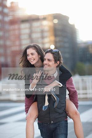 Mid adult man giving girlfriend piggyback in street