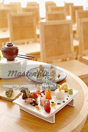 A sushi platter with nigiri, maki, Califormia rolls, tuna, salmon, wasabi and ginger in a restaurant
