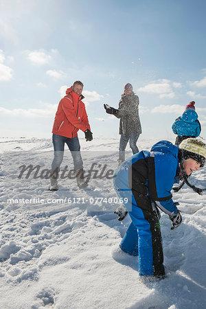 Family having snowball fight, smiling, Bavaria, Germany