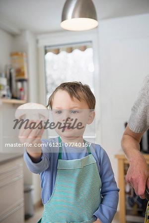 Boy holding mushroom slice in kitchen