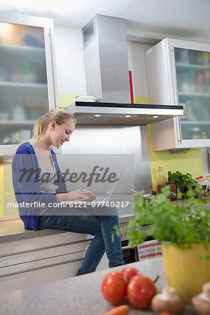 Teenage girl working on laptop in kitchen, smiling