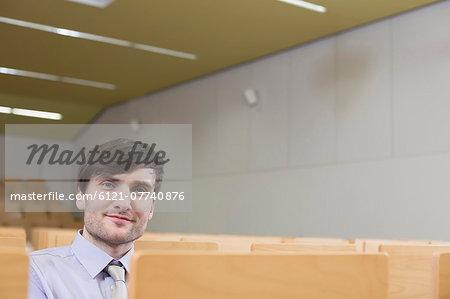 Businessman sitting in auditorium, smiling