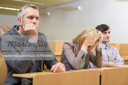 Bored businesspeople sitting in auditorium