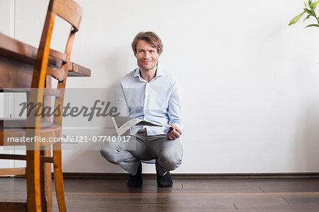 Portrait of mature man holding newspaper, smiling