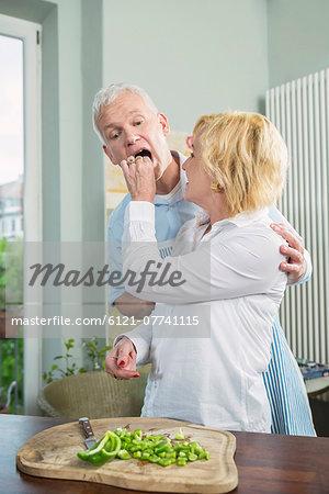 Mature woman feeding food to mature man