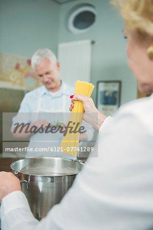 Mature couple preparing pasta