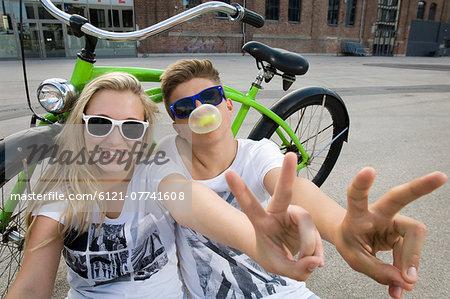 Teenage couple blowing bubble gum