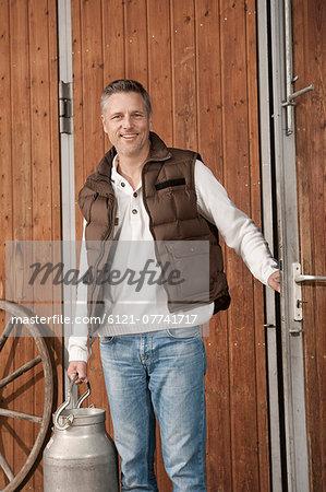 Smiling man holding milk churn on farm
