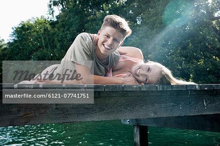 Teenage couple lying on a jetty at a lake