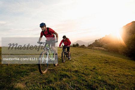 two mountain bikers on the way at sunset, Kolovrat, Istria, Slovenia