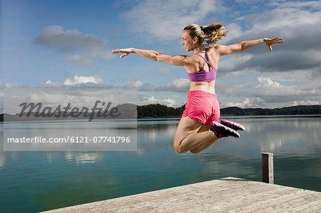 Woman jumping on jetty, Woerthsee, Bavaria, Germany